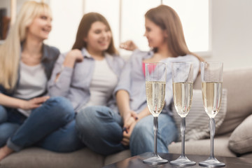 Three young female friends drinking champagne