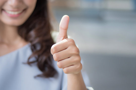 successful girl pointing thumb up; portrait of cheerful smiling woman pointing up approving, yes, ok, good, thumb up gesture; asian woman young adult model
