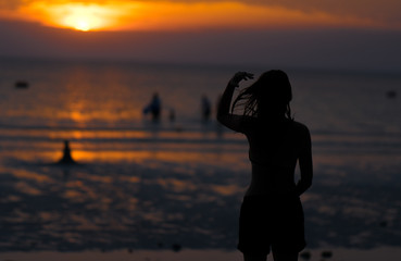 Beautiful sunset with sea and beach.  Blurred people swimming at the sea.