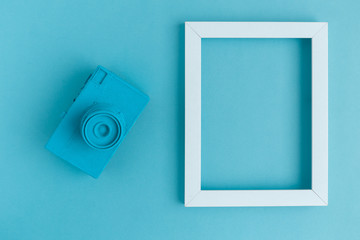 Flat lay of blue vintage camera and photo frame background