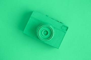 Flat lay of retro camera painted in green surrealism art concept.