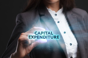 The concept of business, technology, the Internet and the network. A young entrepreneur working on a virtual screen of the future and sees the inscription: Capital expenditure