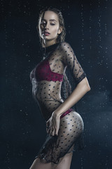 Beautiful wet slim girl wearing a red lingerie and black translucent veil posing sideways in rain water drops in a studio on black background in a theatrical smoke