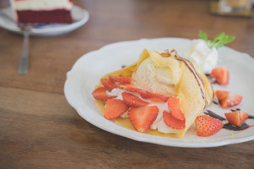 vanilla ice cream with crepes and strawberry on wooden desk,in cafe.