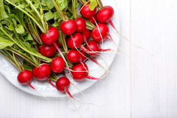 Fresh red radishes with tops in plate on white table. Top view.