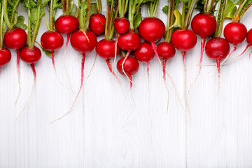 Fresh red radishes with tops in line on white wooden table.