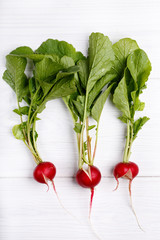 Three split red radishes with tops in line on white background. Top view.