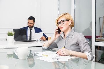 Attractive blonde businesswoman wears eyeglasses talk by phonebefore bearded man working with laptop in modern white office interior