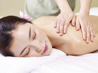 young asian woman receiving massage in spa salon, focus on the masseuse's hands