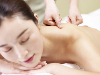 beautiful young asian woman receiving massage in spa salon, focus on the hands