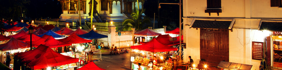 Famous night market in Luang Prabang, Laos with illuminated temple