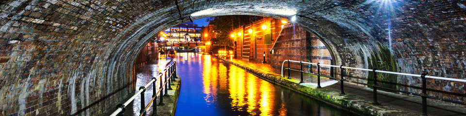 Tunnel in the city center during the rain, illuminated buildings at night, famous Birmingham canal in UK