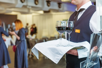 Professional waiter in uniform holding a tray with glasses of vine at business event. Catering or celebration concept. Service at corporate meeting, party, weddings. Selective focus, space for text.