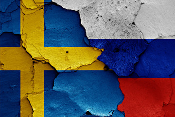 flags of Sweden and Russia painted on cracked wall