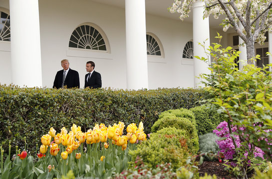 U.S. President Trump and French President Macron walk down the colonnade past the Rose Garden at the at the White House in Washington