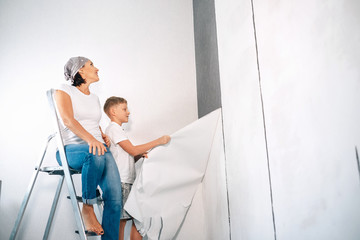Mother and son take off wallpapers together and prepare room for renovation