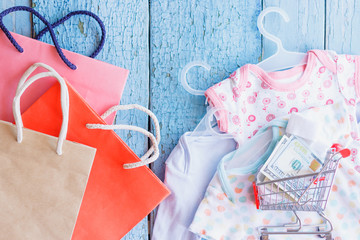 Different clothes for a newborn and a shopping cart