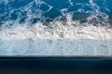 fließendes Wasser am Wehr im Sonnenschein