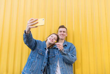 Happy couple doing selfie on a background of yellow wall. A smiling man and girl are photographed on a yellow background. A pair of hipster makes selfie
