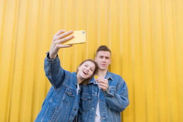 Beautiful young couple makes selfie on a background of yellow wall. Focus on the smartphone. Selfies on the smartphone