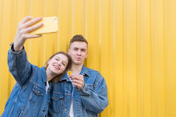 Stylish couple in denim jacket makes selfie on a yellow background. Selfies background color on the wall.