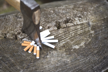 The cigarettes are chopped by an axe on a stump. Smoking cessation.