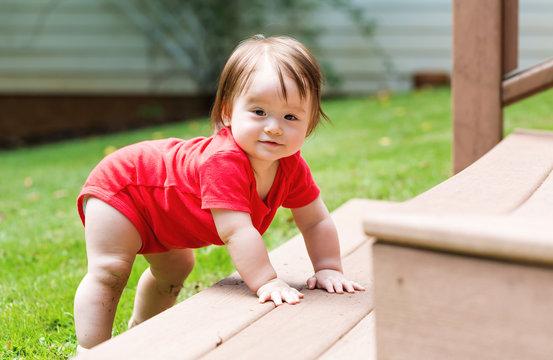 Happy baby boy climbing the backyard stairs