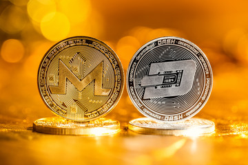Monero and Dash cryptocurrency coins on a golden background