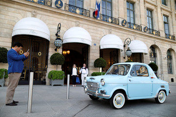 A man stops to photograph a vintage Vespa 400 car that is parked in front of the Ritz Hotel on the Place Vendome in Paris