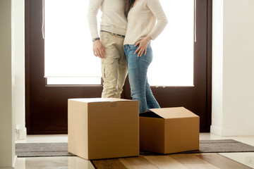 Happy couple embracing standing near cardboard boxes on moving day, homeowners renters tenants just moved in own house, family relocating, buying new home, mortgage loan investment concept, close up