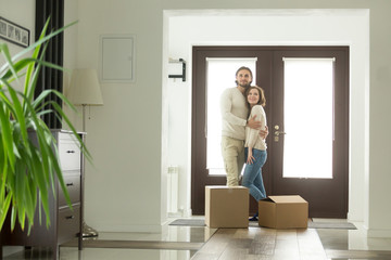 Moving day concept, happy young couple owners hugging embracing in new home standing with boxes in modern hallway of own big luxury house, mortgage loan investment, buying real estate and relocation