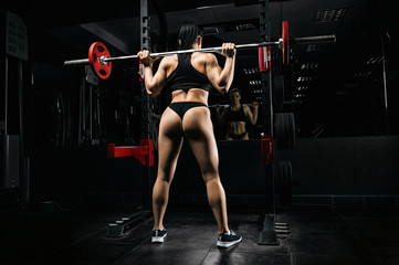 Charming girl is standing in the gym with a barbell on her shoulders.