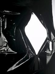 Black latex zippered bag on white background