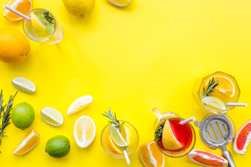 Bartender workplace for make fruit cocktail with alcohol. Strainer near citrus fruits and glass with cocktail on yellow background top view copy space