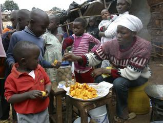 Children wait in line to get free fried potatoes from woman in sprawling Kibera slums in Kenya's capital Nairobi