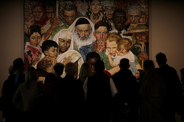 A tour group looks at 'The Golden Rule Mosaic', a work based on a painting by Norman Rockwell as they visit United Nations Headquarters in New York City