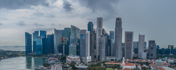 Aerial drone view of Singapore skyscrapers with city skyline during cloudy summer day