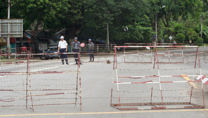Security officers stand near barricades erected along University Avenue in Yangon