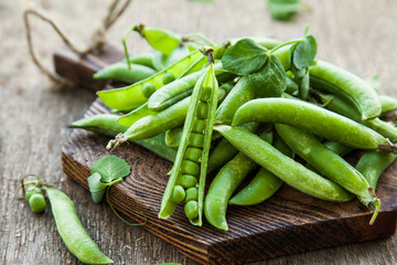 Green peas in pods on a wooden table