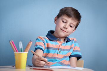 Cheerful smiling Caucasian boy spending time drawing with colorful pencils.