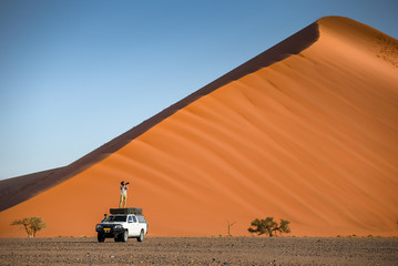 Young Asian man traveler and photographer standing on camper car near orange sand dune. Travel desert concept