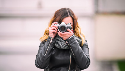 Photographer girl in leather coat with a vintage DSLR camera