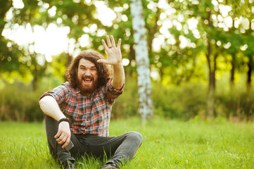 Bearded man. Smiling man with beard outside sitting on grass and making Hello Gesture
