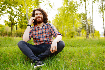 Cheerful smiling bearded man sitting on grass in park and talking on the phone