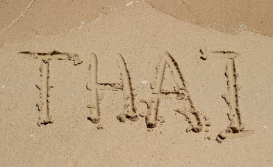 Inscription on the wet sand. Hand inscription Thai on a wet sand in sunny day