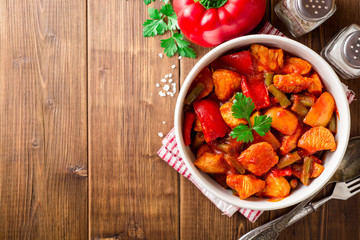 Turkey stew with bell peppers, green beans and tomatoes in bowl on dark wooden table