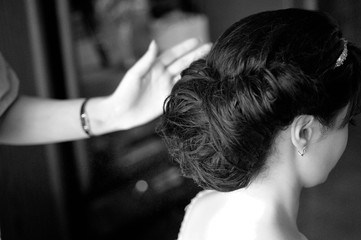 Morning gathering of the bride. The stylist prepares the bride for the wedding. Hair styling with hair spray. Black and white.