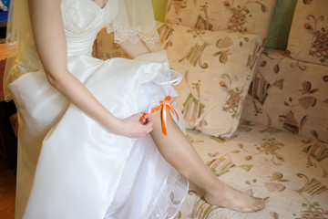 The bride in a wedding dress puts on a garter on the leg.