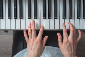 Top view of women's hands playing the synthesizer, composing music