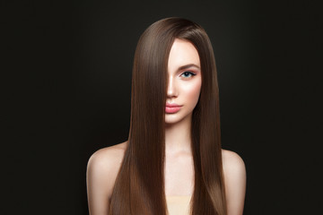 Beautiful woman portrait on black background with beautiful straight hair.